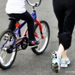 Mom Running Along with Child on Bike