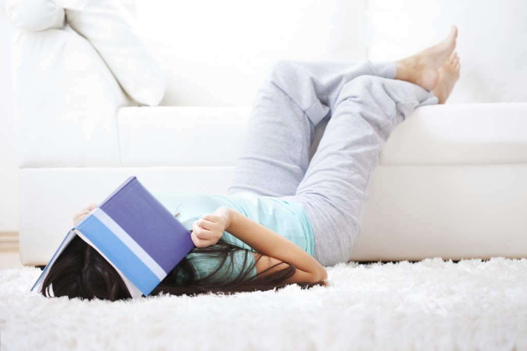 Woman laying with book over her face